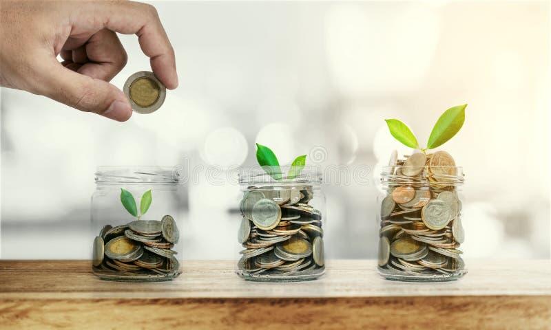 Übergeben Sie das Einsetzen der Münze in Glasflaschen mit den glühenden Anlagen, Rettungsgeld und Investitionskonzepten lizenzfreie stockbilder