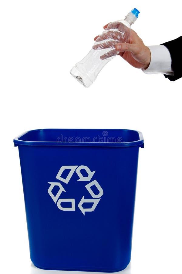 Übergeben Sie das Einsetzen einer Wasserflasche in einen recylce Behälter lizenzfreie stockfotografie