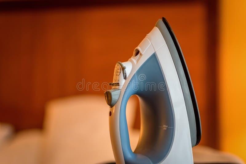Übergeben Sie das Eisen, das in der aufrechten Position auf Bügelbrett in Hauptl stillsteht stockfotos