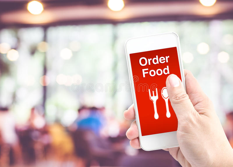 Übergeben Sie das Halten beweglich mit Bestellungslebensmittel mit Unschärferestaurant backgro stockfotos
