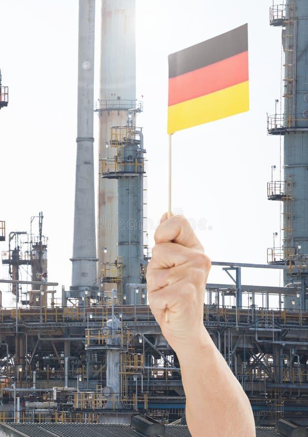 Übergeben Sie das Halten der deutschen Flagge vor industriellem FabrikKraftwerk lizenzfreie stockfotografie