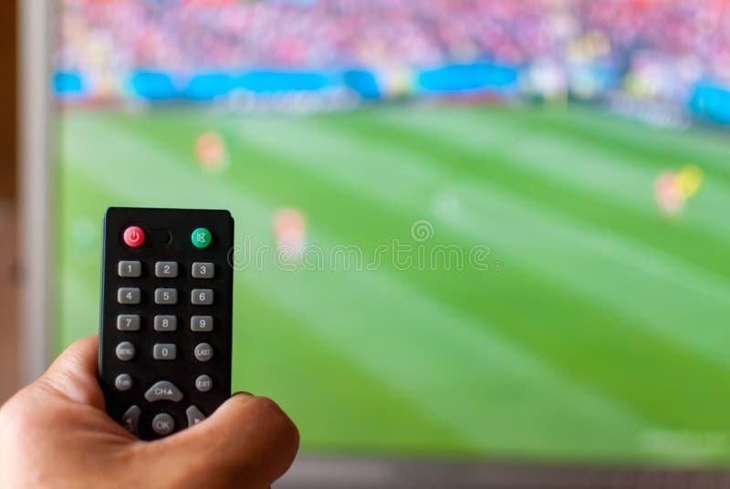Übergeben Sie das Halten der Fernbedienung des Fernsehens gegen den unscharfen Schirm, auf dem Sendungsfußball lizenzfreie stockfotos
