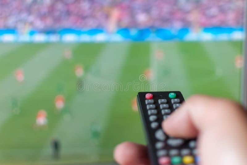 Übergeben Sie das Halten der Fernbedienung des Fernsehens gegen den unscharfen Schirm, auf dem Sendungsfußball stockfotos