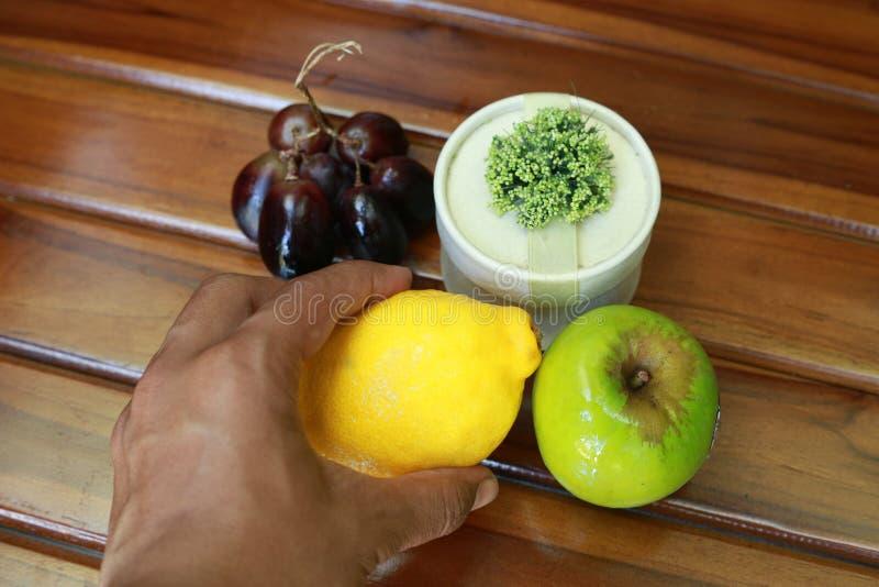 Übergeben Sie das Halten der gelben Zitrone, der Trauben und des grünen Apfels lokalisiert auf hölzernem Hintergrund stockfotos