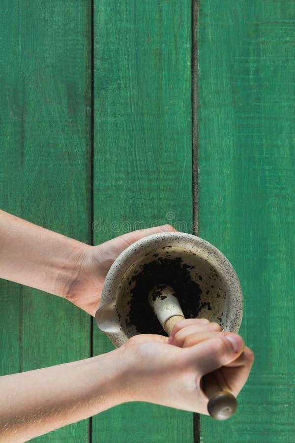 Übergeben Sie das Halten der Krautpaste im Mörser und in der Stampfe stockbild