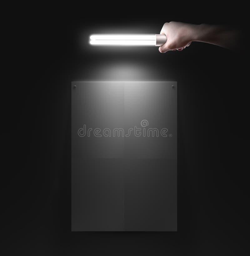 Übergeben Sie das Halten der Lampe nahe der Wand mit leerem Plakatmodell lizenzfreies stockfoto