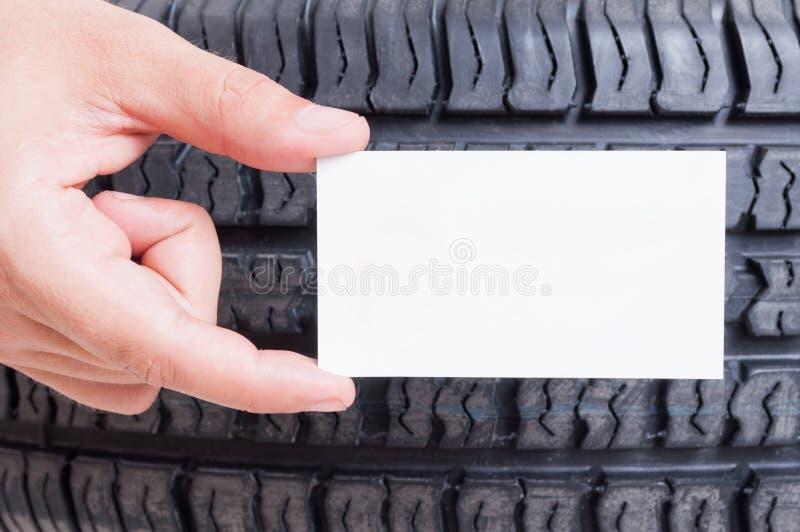 Übergeben Sie das Halten der leeren Karte auf Autorad-Reifenhintergrund lizenzfreies stockbild