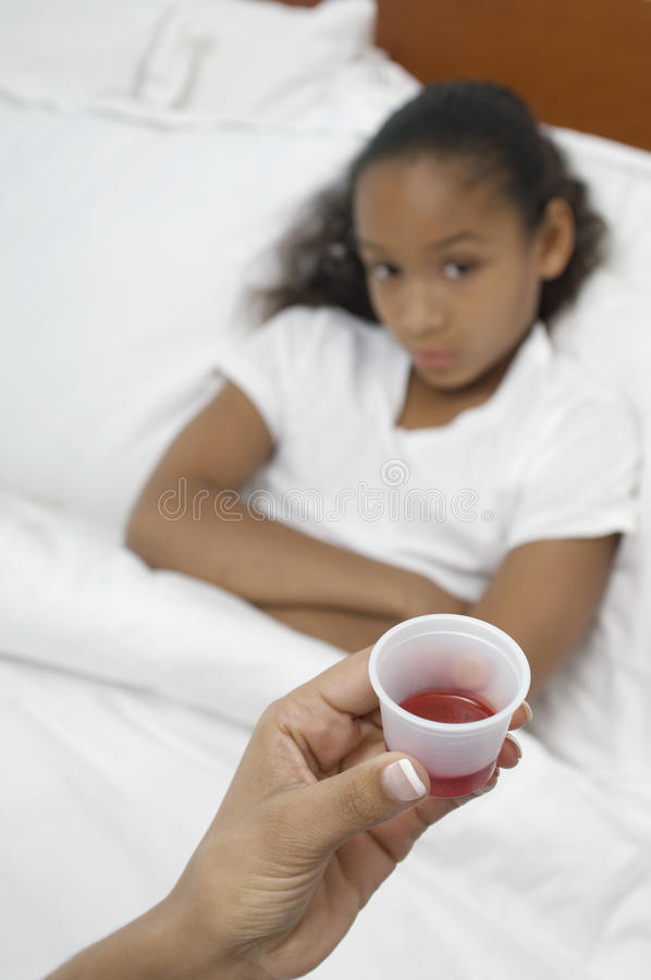 Übergeben Sie das Halten der Medikation für das Mädchen, das im Bett liegt stockbild