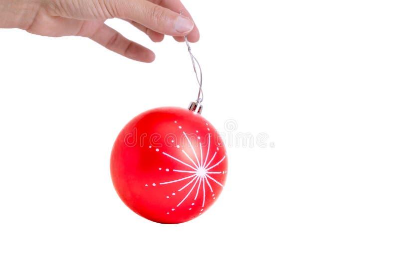 Übergeben Sie das Halten der roten festlichen Weihnachtsverzierung, bereit, am Baum zu hängen lizenzfreie stockbilder