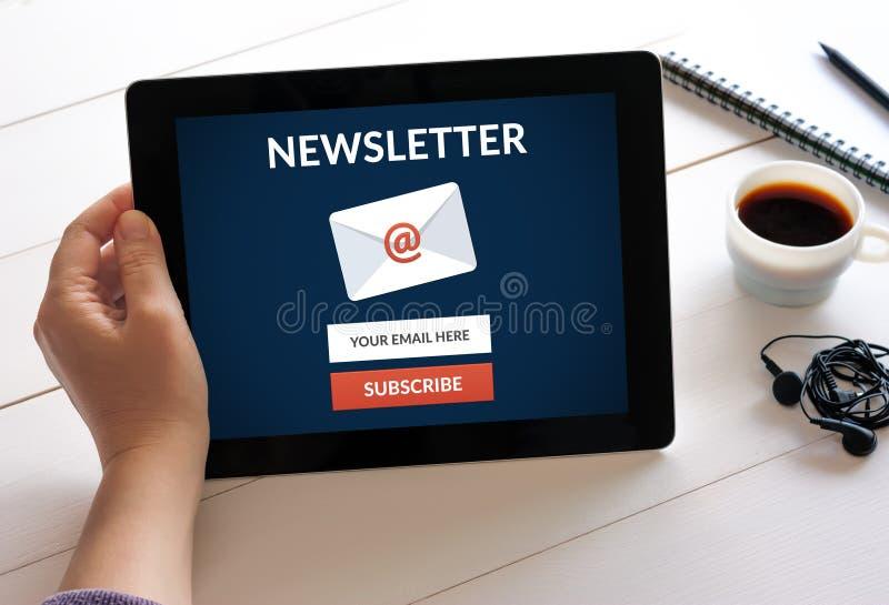 Übergeben Sie das Halten der Tablette mit unterzeichnen Newsletterkonzept auf Schirm