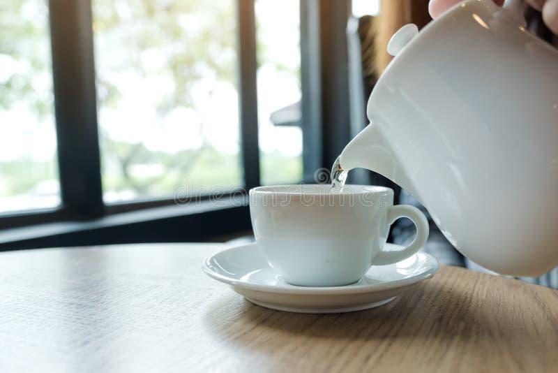 Übergeben Sie das Halten der Teekanne und das Gießen des Tees in eine weiße Schale auf Holztisch stockfoto