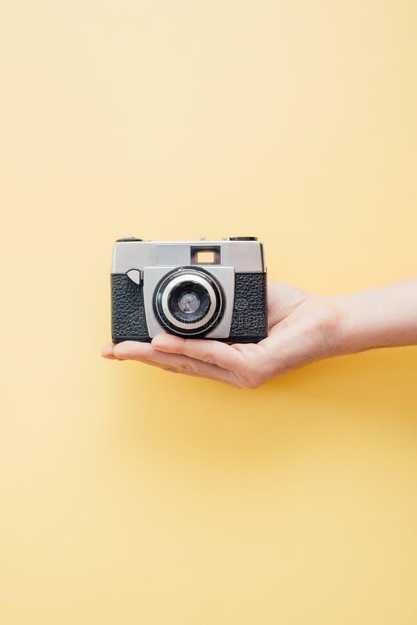 Übergeben Sie das Halten der Weinleseartkamera auf gelbem Hintergrund lizenzfreie stockfotografie