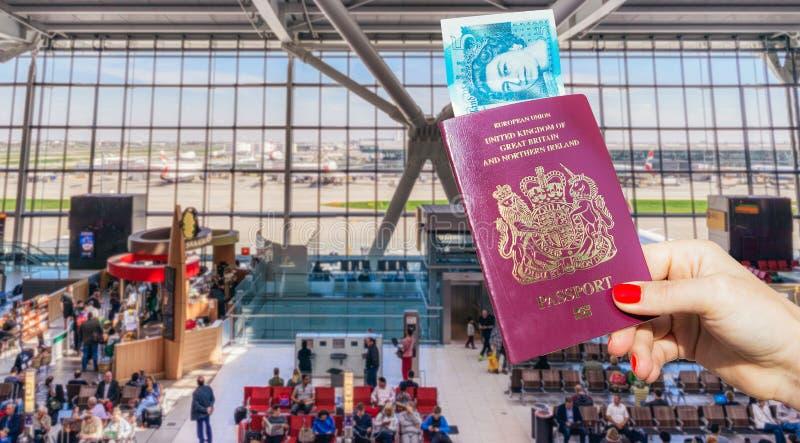 Übergeben Sie das Halten des BRITISCHEN Passes und des Großbritanniens eine 5-Pfund-Anmerkung lizenzfreies stockfoto