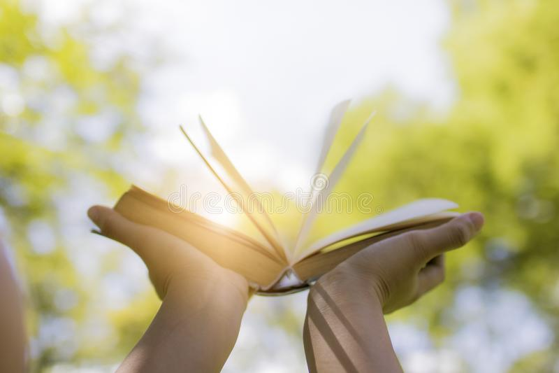 Übergeben Sie das Halten des Buches auf Himmel, Wissen und Klugheitskonzept lizenzfreies stockfoto