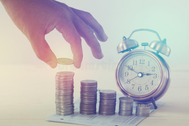 Übergeben Sie das Halten des Geldes auf Stapel von Münzen und von Weckerkonzept in der Abwehr lizenzfreies stockfoto