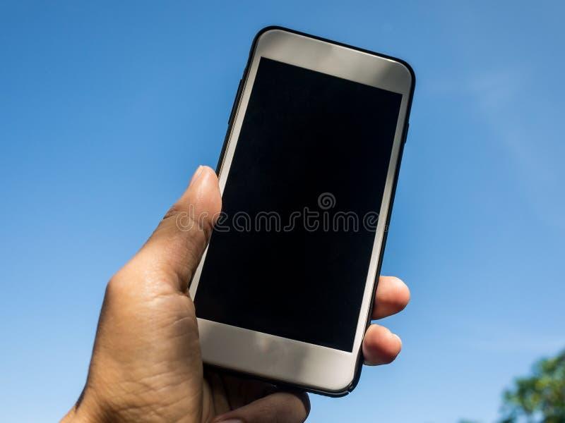 Übergeben Sie das Halten des intelligenten Mobiltelefons mit Himmelhintergrund lizenzfreie stockbilder