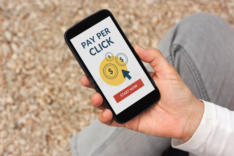 Übergeben Sie das Halten des intelligenten Telefons mit Bezahlung-pro-Klick- Konzept auf Schirm stockbild