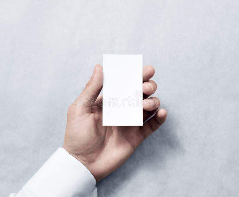 Übergeben Sie das Halten des leeren vertikalen weißen Visitenkartedesignmodells stockfotos