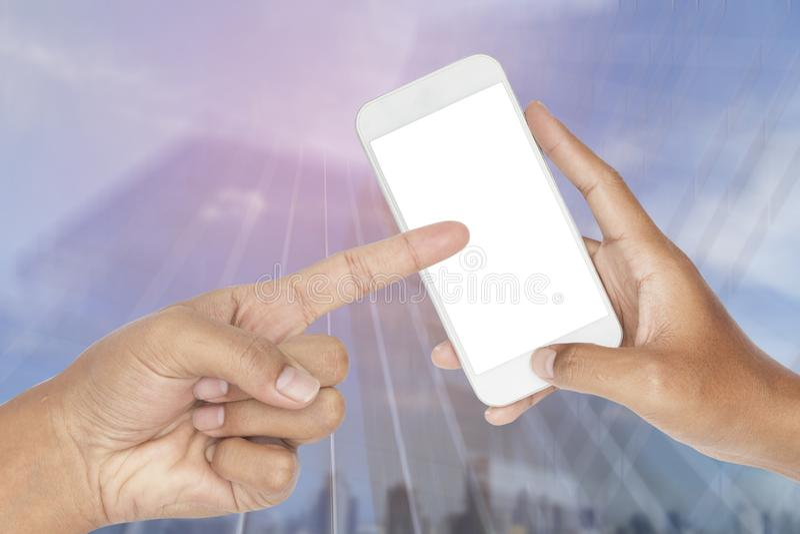 Übergeben Sie das Halten des modernen intelligenten Telefons mit Zusammenfassung unscharfer Bewegung des modernen Glasgebäudes lizenzfreie stockbilder