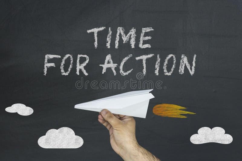Übergeben Sie das Halten des Papierflugzeuges und des Textes geschrieben auf Tafel: Zeit für Aktion stockfotos
