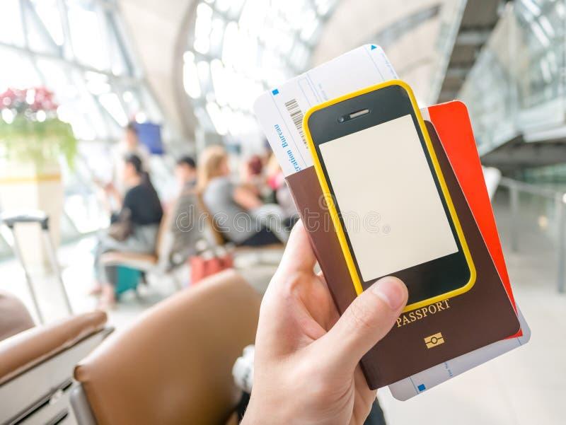 Übergeben Sie das Halten des Passes, der Bordkarte und des intelligenten Telefons im Flughafen lizenzfreies stockbild