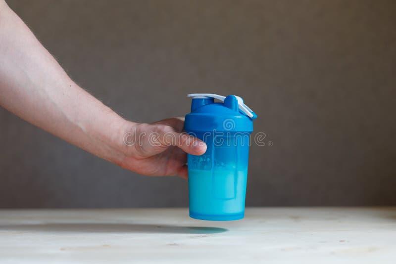 Übergeben Sie das Halten des Plastikschüttels-apparat mit Proteindrink und des Glases auf Tabelle Die Faust des Mannes, die das B stockfoto