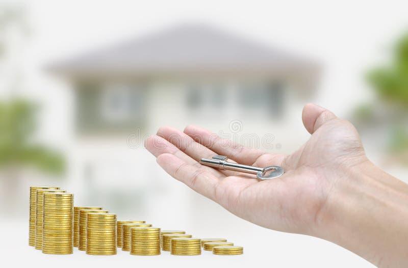 Übergeben Sie das Halten des Schlüssels und der Goldmünze auf Haushintergrund lizenzfreie stockfotos
