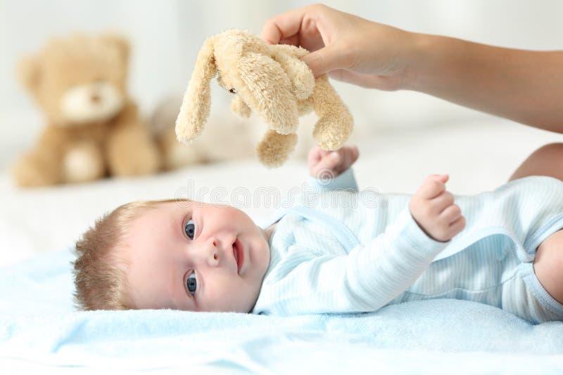 Übergeben Sie das Halten des Teddybären und des Babys Sie betrachtend lizenzfreies stockfoto