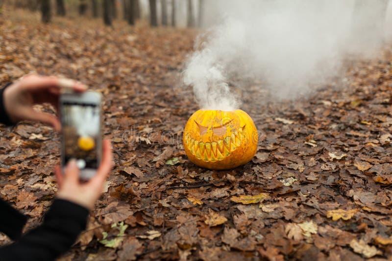Übergeben Sie das Halten des Telefons und das Machen des Fotos des Kürbises und des Blattes Blogging Konzept Instagram Halloween  lizenzfreie stockfotos