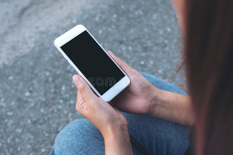 Übergeben Sie das Halten des weißen Handys mit leerem schwarzem Schirm beim Sitzen auf der Straße lizenzfreie stockfotos