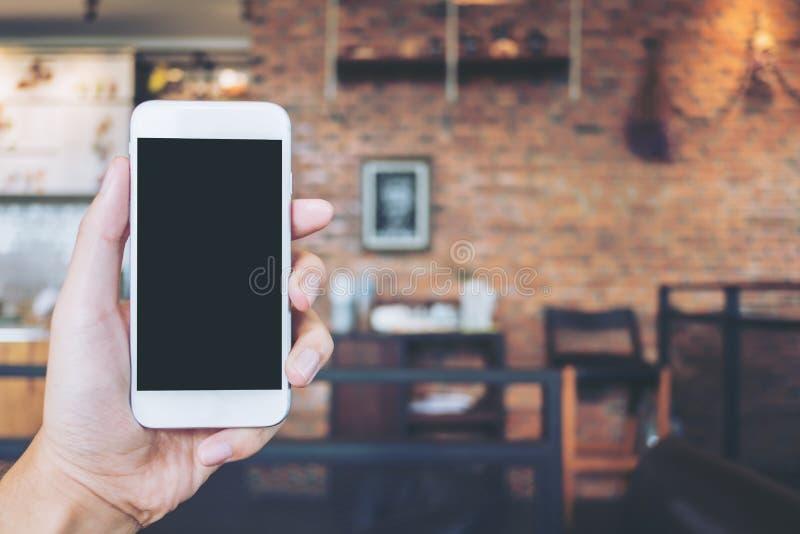 Übergeben Sie das Halten des weißen Handys mit leerem schwarzem Schirm im modernen Dachbodencafé stockfoto