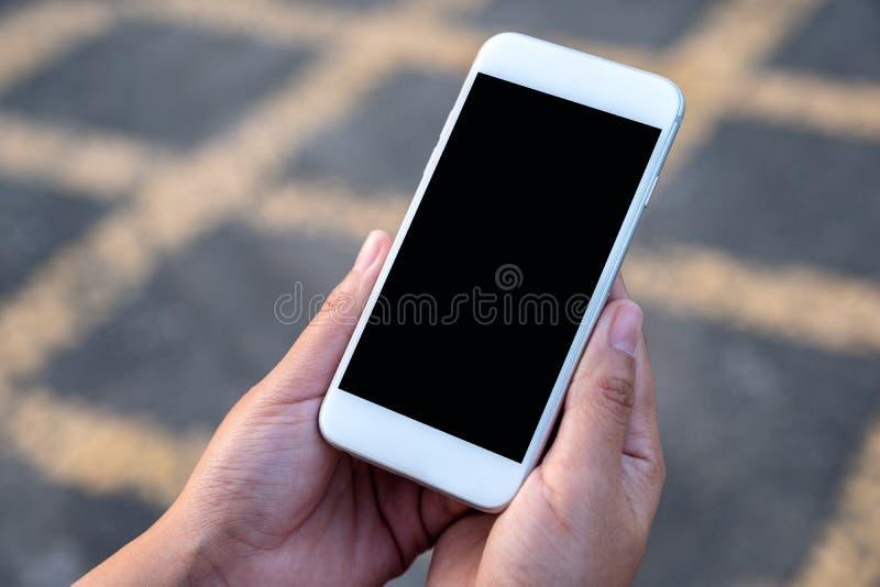 Übergeben Sie das Halten des weißen Handys mit leerem schwarzem Schirm mit Straßenhintergrund lizenzfreie stockbilder