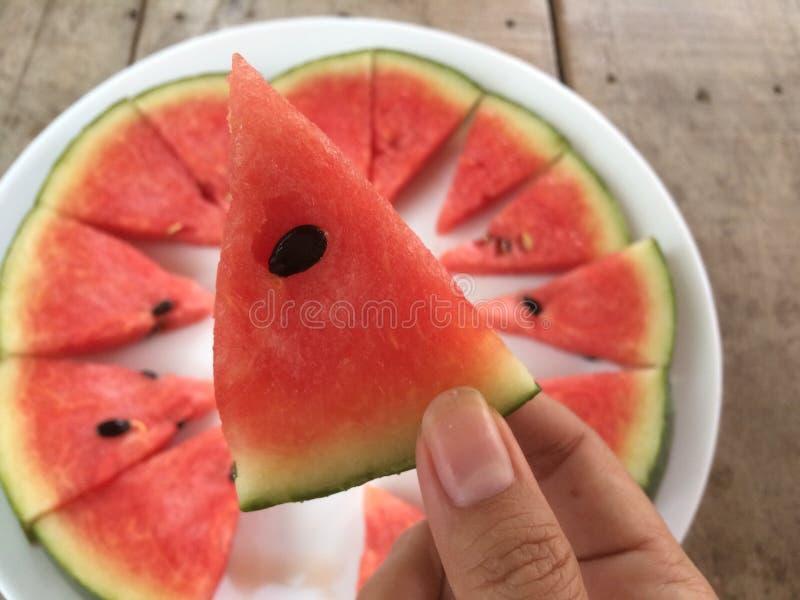 Übergeben Sie das Halten eines Stückes der geschnittenen reifen Wassermelone, Draufsicht stockfoto