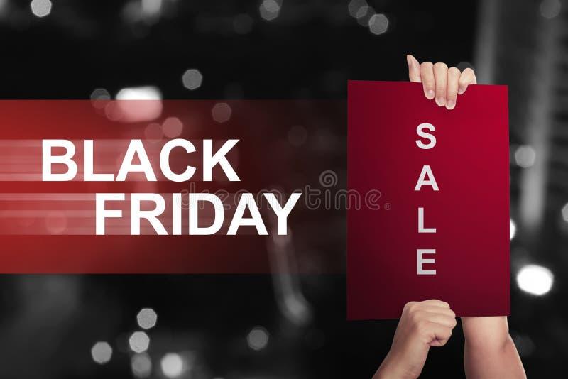 Übergeben Sie das Halten Papier mit Verkaufstext auf Black Friday stockbild