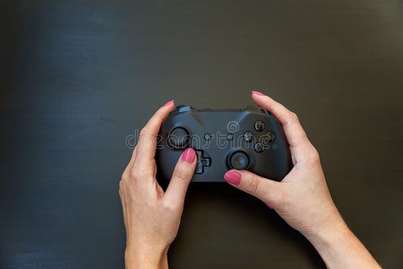 Übergeben Sie das Halten schwarzen Steuerknüppel gamepad auf schwarzem Hintergrund lizenzfreie stockbilder