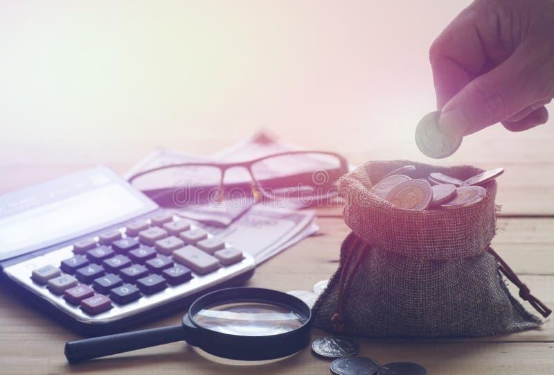 Übergeben Sie das Halten von Münzen auf Tasche, Sack der Abwehr mit Taschenrechner lizenzfreies stockbild