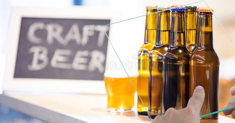 Übergeben Sie das Machen des Fotos der Bierflaschen durch transparentes Gerät an der Bar stockbilder