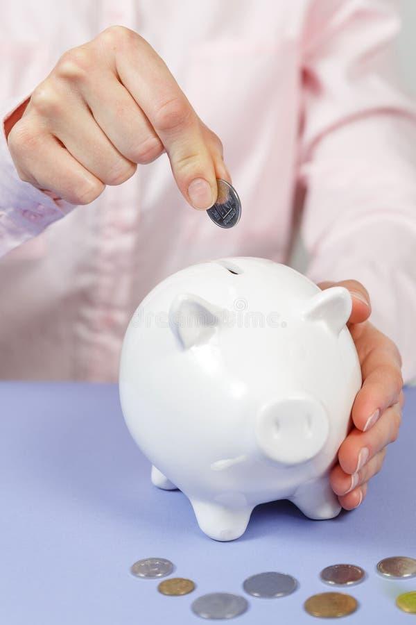 Übergeben Sie das Setzen der Münze in Sparschweinnahaufnahme Selektiver Fokus stockbild