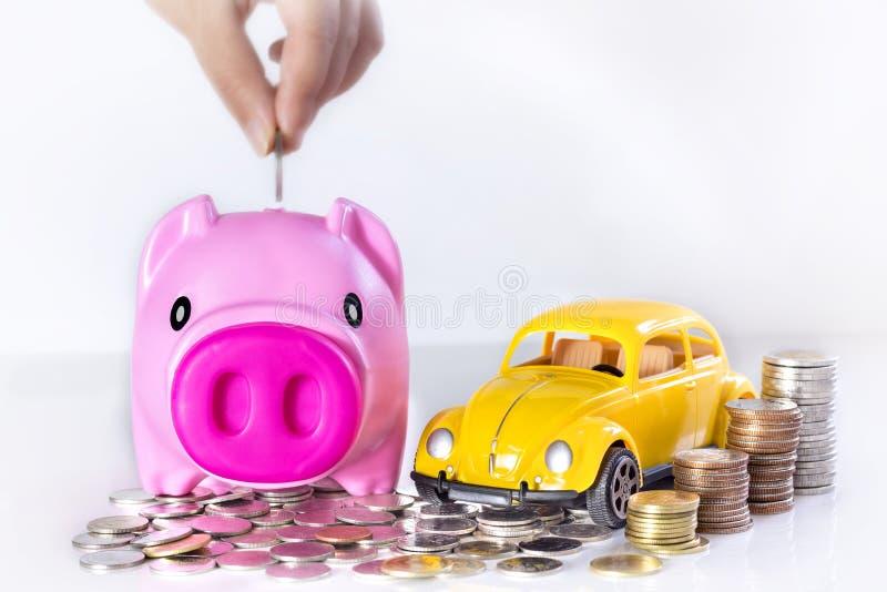 Übergeben Sie das Setzen einer Münze in das Sparschwein mit einem Auto des Spielzeugs und der Co lizenzfreie stockfotos