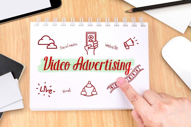 Übergeben Sie das Zeigen auf Videowerbung auf Buch mit Hand gezeichnetem featu lizenzfreie stockfotos