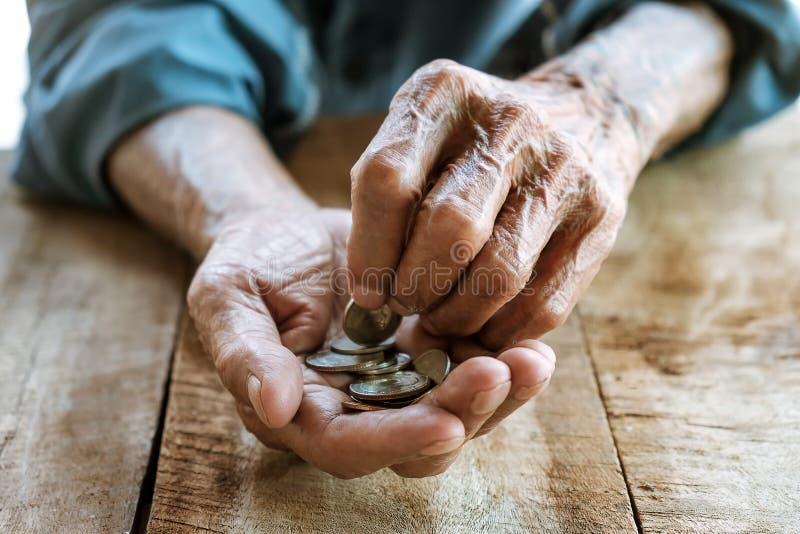 Übergeben Sie den alten Mann, der um Geld wegen des Hungers bittet stockfotos