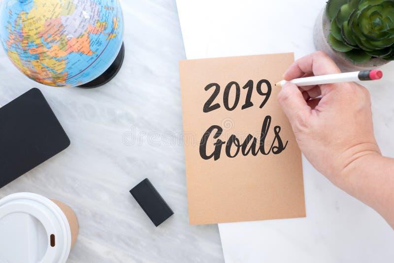 Übergeben Sie den Behälter, der 2019 Ziele auf braunes Papier mit blauem glo schreibt lizenzfreies stockbild