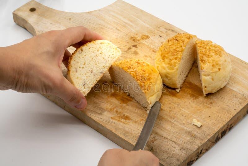 Übergeben Sie den Schnitt des ganzen Brötchens mit Samen des indischen Sesams auf hölzernem quadratischem cuttin stockfoto