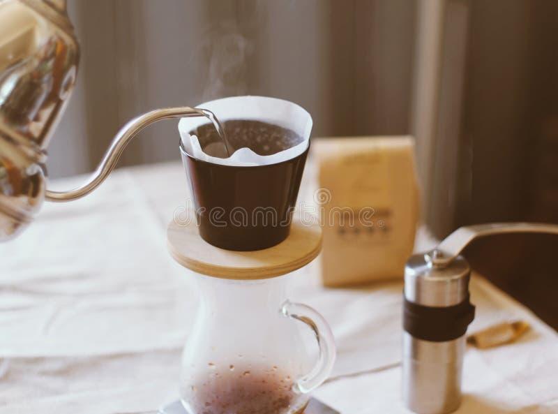 Übergeben Sie den Tropfenfängerkaffee und Wasser auf Kaffeesatz auslaufen lizenzfreies stockbild