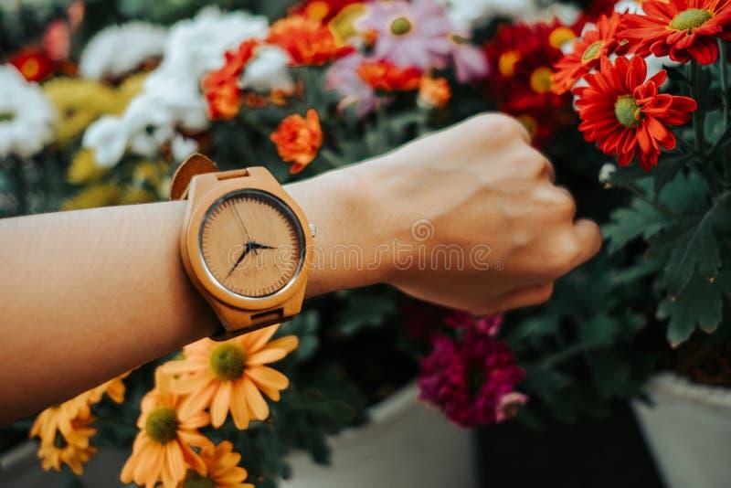 Übergeben Sie die Geschäftsfrau, die hölzerne Uhr mit Kopie Raum und bea trägt lizenzfreies stockfoto