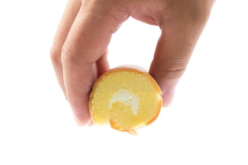 Übergeben Sie ein Stück des Kuchens in der Mitte mit Sahne halten stockbilder