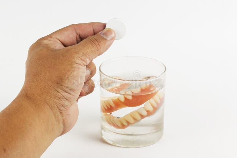 Übergeben Sie einem Glas von falschem Teet das Halten von Reinigungstabletten lizenzfreies stockbild