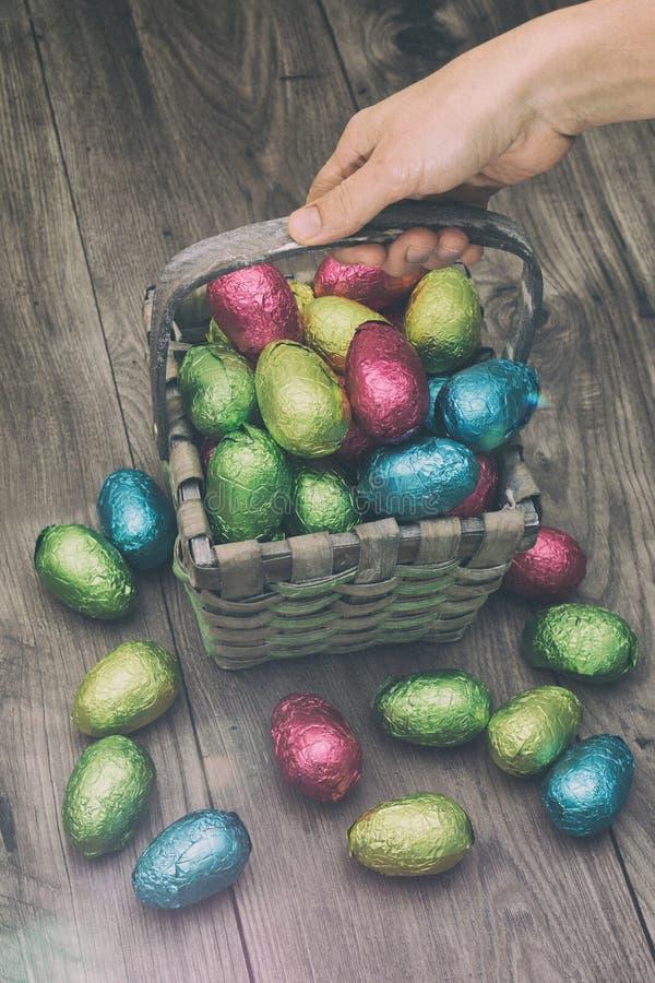 Übergeben Sie einen Strohkorb aufheben, der mit den Ostern-Schokoladeneiern gefüllt wird, die in der bunten Alufolie eingewickelt lizenzfreie stockfotos