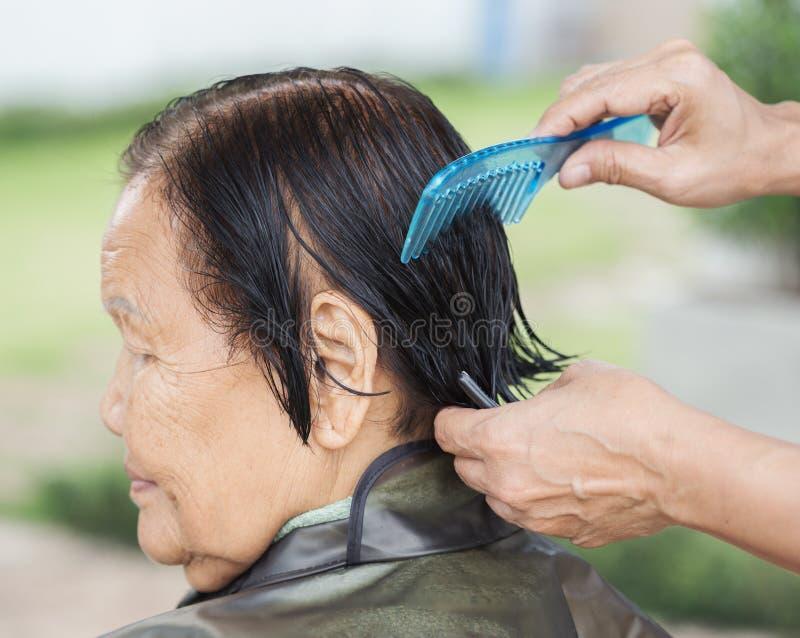 Übergeben Sie Gebrauchskamm zum Kleiden des Haares einer älteren Frau lizenzfreie stockfotos