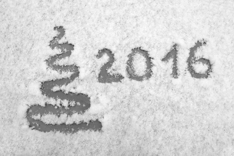 Übergeben Sie 2016 geschrieben und extrahieren Sie Weihnachtsbaum auf Schnee Neues Jahr und Weihnachtskarte Kann in allen möglich lizenzfreie stockfotografie